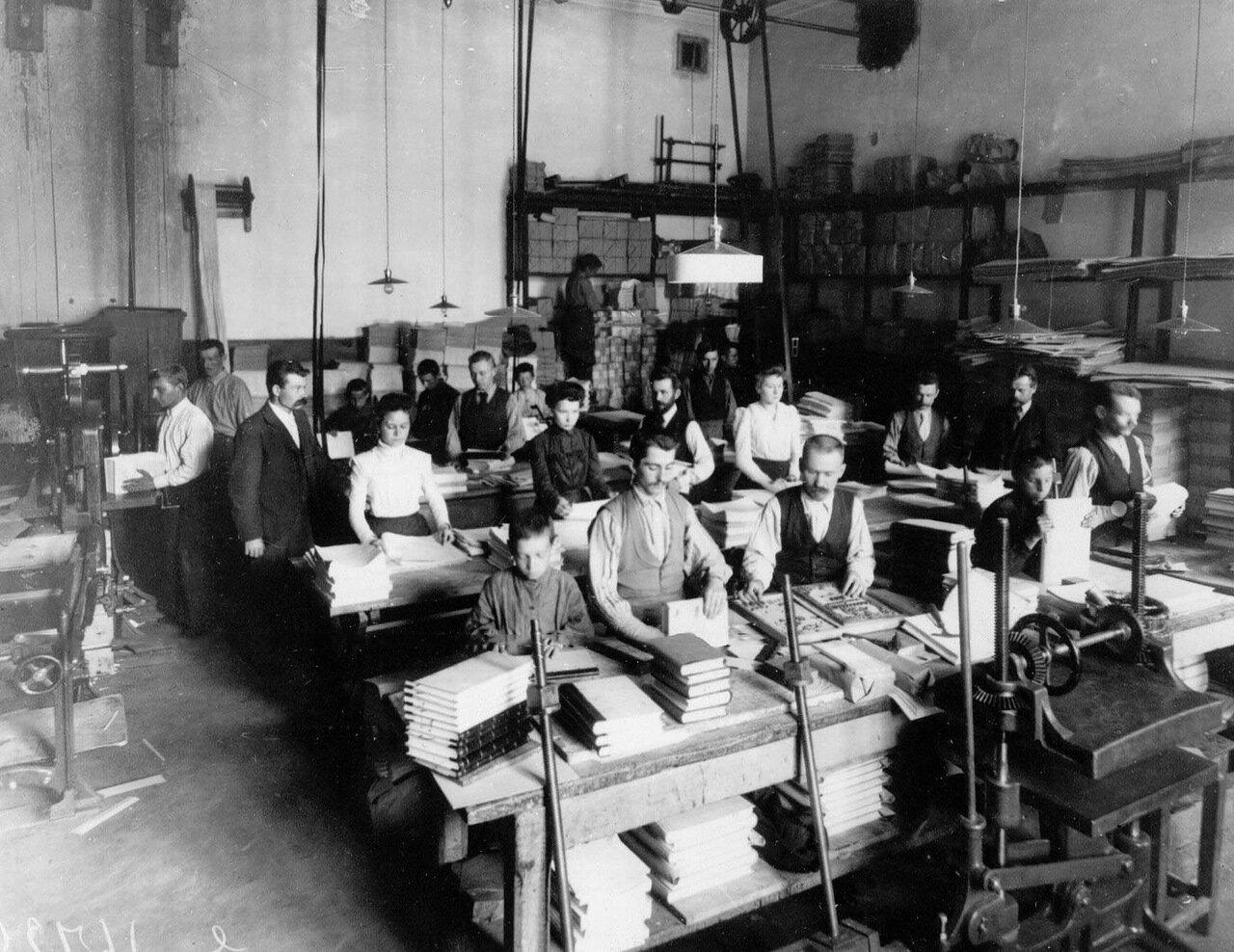 Сотрудники цеха послепечатной обработки изготавливают ежедневники на 20-й год