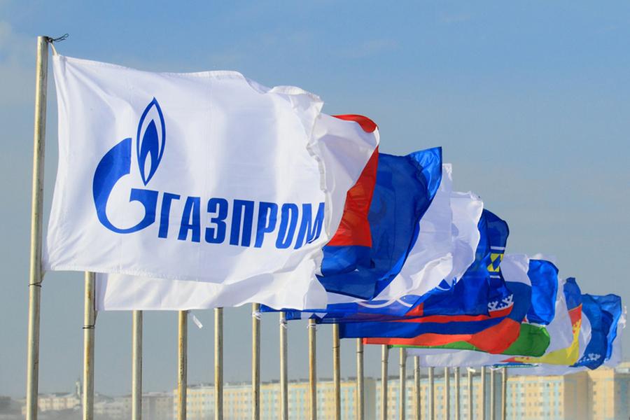 Флаг ОАО Газпром на фоне неба и флагов городов Ямала